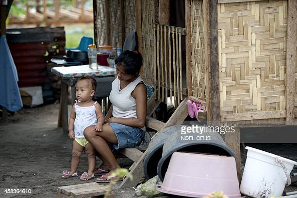 To go with PhilippinestyphoonpovertychildrenFEATURE by Karl Malakunas In this picture taken on October 17 Emily Sagalis sits with her baby girl in...
