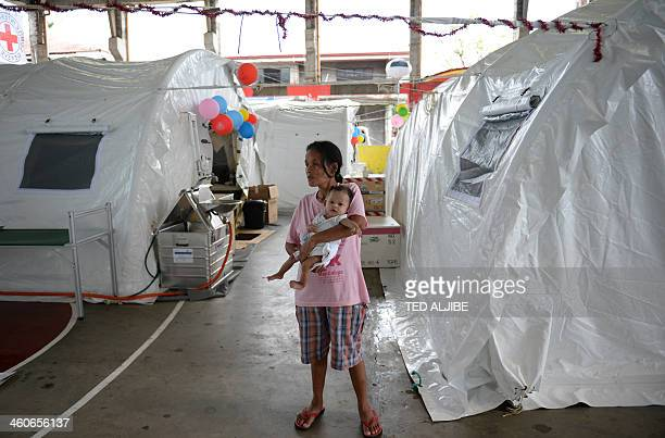 To go with PhilippinesweathertyphoonhealthRedCross by Cecil MORELLA This photo taken on December 24 2013 shows a mother babysitting her child next to...