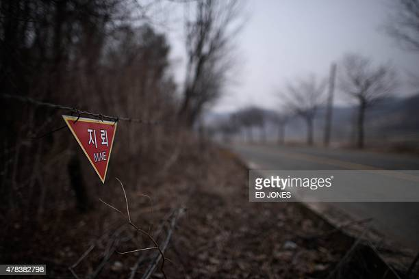 To go with SKOREAMILITARYLANDMINE by Jung HaWon A photo taken on March 17 2015 shows a sign warning of landmines in woodland near the Demilitarized...