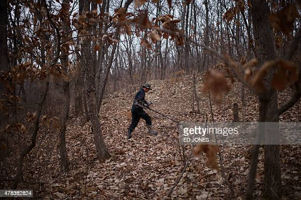 To go with SKOREAMILITARYLANDMINE by Jung HaWon In a photo taken on March 17 Kim KiHo head of the Korea Research Institute for Mine Clearance hunts...