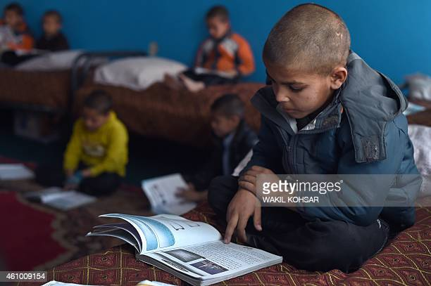 To go with story 'AfghanistanunrestchildrenorphanageFOCUS' by Emmanuel PARISSE In this photograph taken on December 17 Afghan children read school...