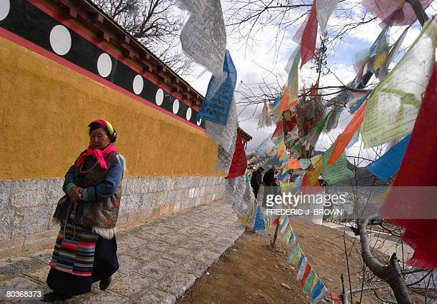 """To Go with story """"China-Unrest-Tibet-Rights-Yunnan-Shangrila"""" by Robert Saiget A Tibetan woman holds her prayer beads while walking past prayer flags..."""