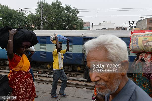 To go with story 'Indiaeconomytransportrail' by Annie Banerji In this photograph taken on June 29 2014 Indian passengers walk on the railway platform...