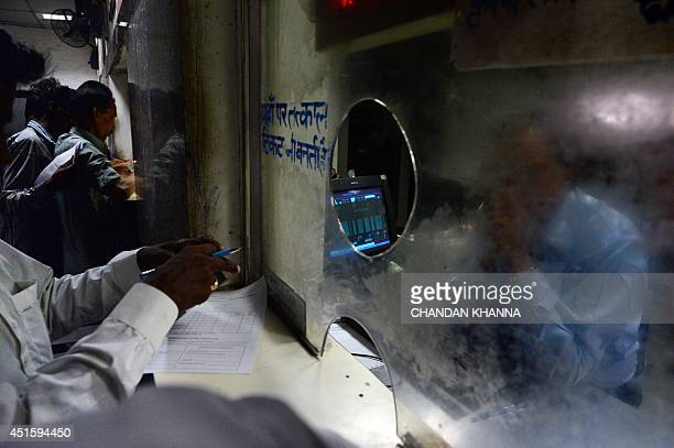 To go with story 'Indiaeconomytransportrail' by Annie Banerji In this photograph taken on June 29 2014 a passenger fills in a form at the reservation...