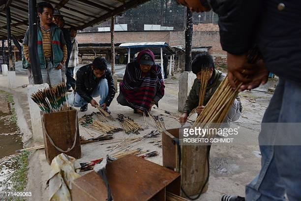 To go with story 'Indiagamblingarcherytradition' In this photograph taken on February 2 2013 Indian men arrange arrows by the color of their feathers...