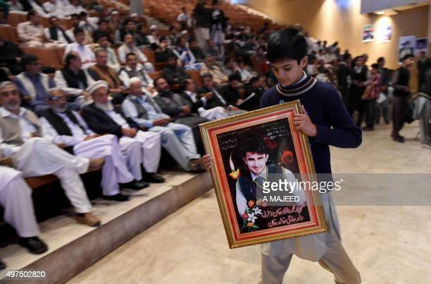 To go with story 'PakistanFranceunrestattacks' In this photograph taken on November 16 a Pakistani boy carries a picture of his brother who was...