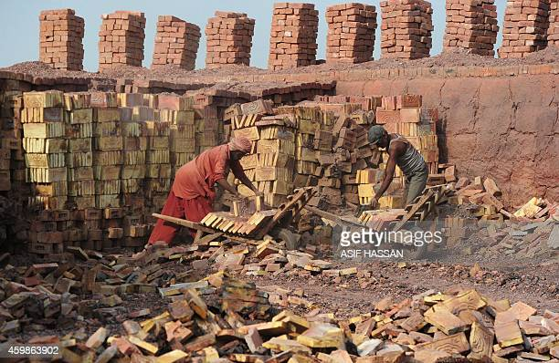 To go with story 'PakistanLabourRightsSlavery' by Guillaume Lavallee In this photograph taken on November 10 2014 Pakistani labourers load bricks...