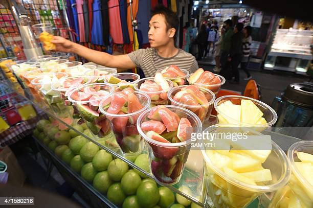 To go with Taiwanfoodlifestyledesign FEATURE by Laura MANNERING In this photo taken on April 13 a vendor holds a cup of fruit at the Raohe night...