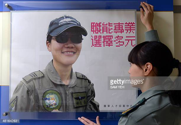 To go with TaiwansocialemploymentwomenFEATURE by Amber WANG In this picture taken on March 20 a female sargent adjusts an advertisement at the...
