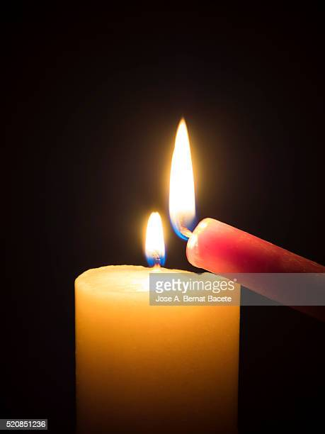 To ignite a candle sharing the flame