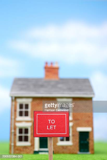'To Let' sign outside model house (focus on sign)