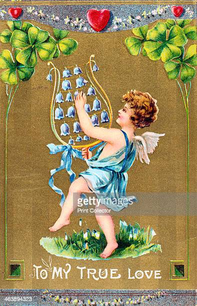 'To My True Love' American Valentine card c1910 Cupid dances on grass with naturalised Snowdrops and is playing a lyre of bluebells Above him are red...
