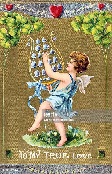 To My True Love c1910 American Valentine card Cupid dances on grass with naturalised Snowdrops and is playing a lyre of Bluebells Above him are red...