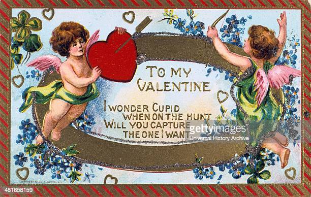 To My Valentine' American Valentine card c1908 Cupid shoots an arrow into a heartheld up by a putto The words are surrounded by garlands of...