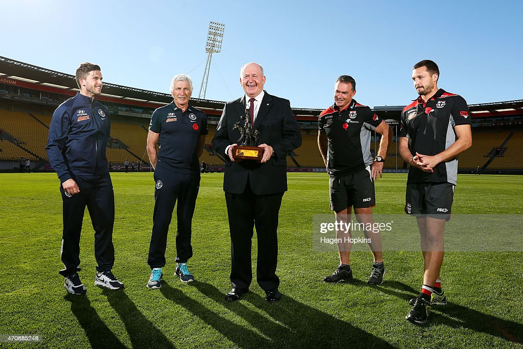 L to R, Captain Marc Murphy and coach Mick Malthouse of Carlton, Australian Governor-General Sir Peter Cosgrove, coach Alan Richardson and captain Jarryn Geary of St Kilda with The Simpson-Henderson Trophy after team training sessions at Westpac Stadium on April 24, 2015 in Wellington, New Zealand.