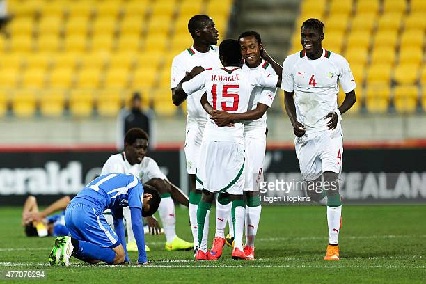 L to R Javokhir Sidikov of Uzbekistan looks dejected while Andelinou Correa Moussa Wague Moussa Ba and Mouhameth Sane of Senegal celebrate at the...