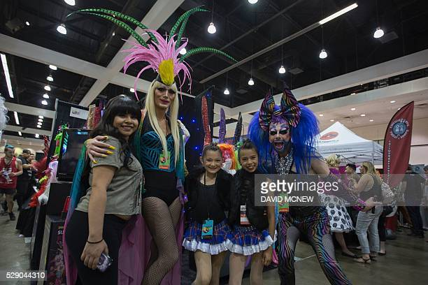 Sisters Bryana 10yearold Beverlynn and 11yearold Tiffany Gonzalez pose for a picture by their mother with drag queens during RuPaul's DragCon at the...