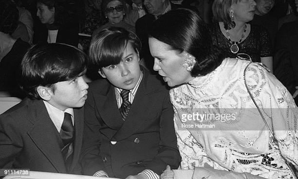 Sons Anderson Cooper and Carter Vanderbilt Cooper lean in to listen to their mother Swissborn socialite Gloria Vanderbilt while attending her fashion...
