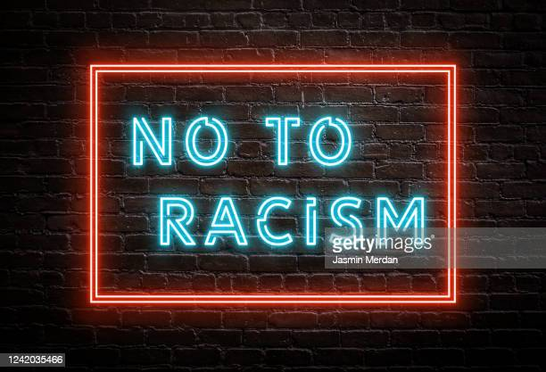 no to racism - neon message on brick wall - anti racism stock pictures, royalty-free photos & images