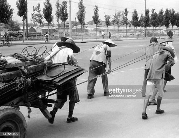 To the eastern edge of Eternal Peace Street Chinese people dragging a big load Beijing 1961