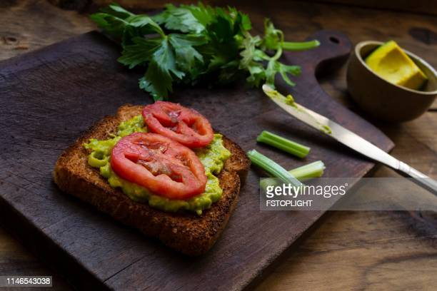 Toast bread with avocado and slice of tomato.