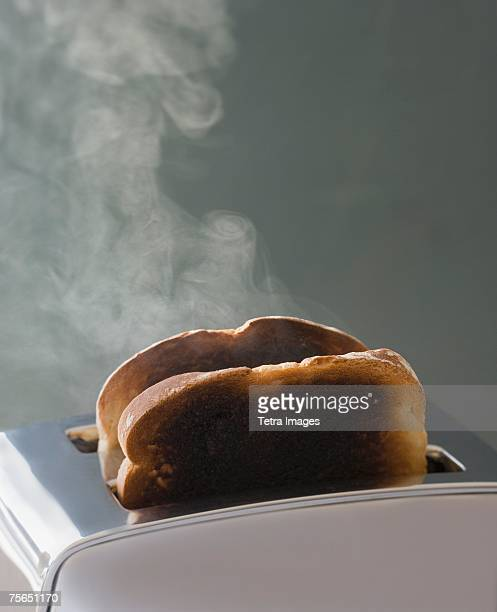 toast burning in toaster - burnt stock pictures, royalty-free photos & images