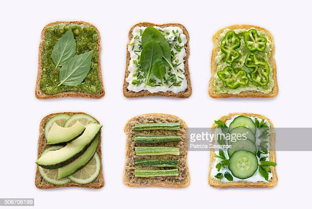 toast of green vegetables in a row on white backgr - avocado toast stockfoto's en -beelden