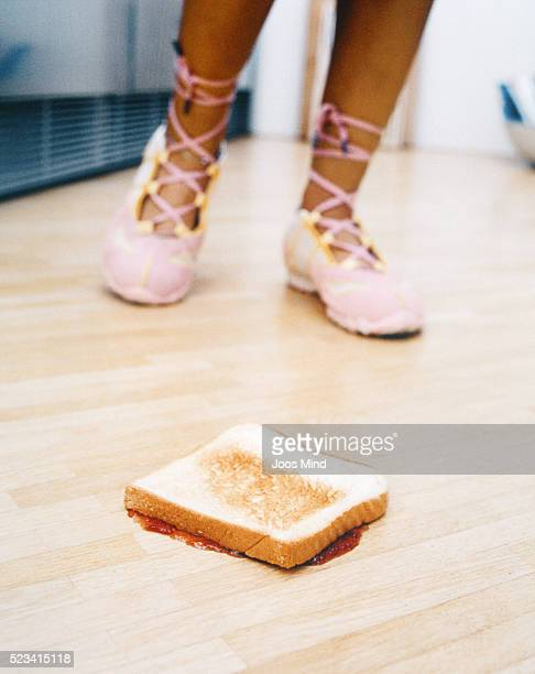 toast on floor with young woman in background - frau gespreizte beine stock-fotos und bilder