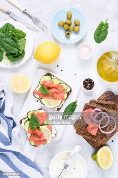 Toast sandwiches with salmon, cream cheese, olives and cucumber on white table