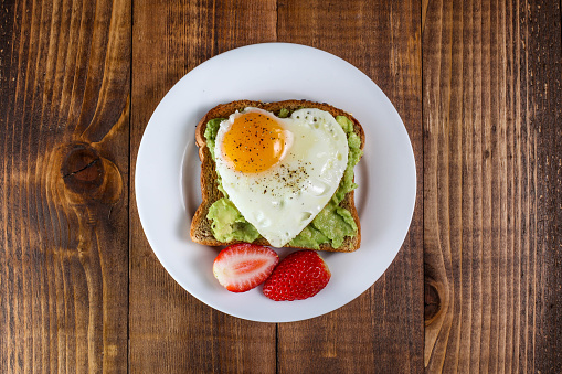Toast with avocado and egg in heart shape 1046693924