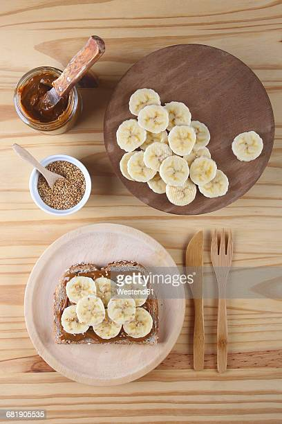 Toast with Dulce de Leche, banana slices and sesame seeds on wooden plate and table