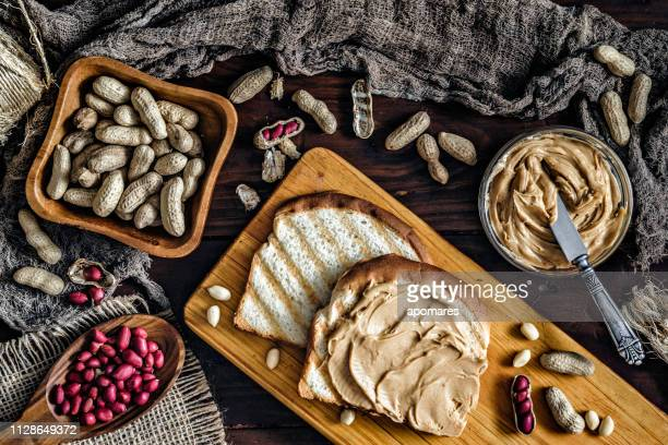 toast with peanut butter on vintage table set in rustic kitchen - peanut butter and jelly sandwich stock pictures, royalty-free photos & images
