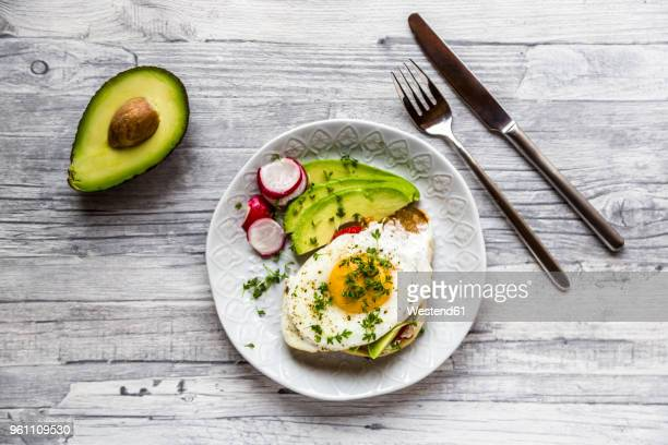 Toast with with fried egg, avocado, red radish, tomato and cress