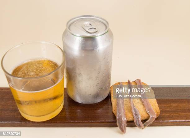 Toasted Bread with anchovies, beer Can and glass of beer
