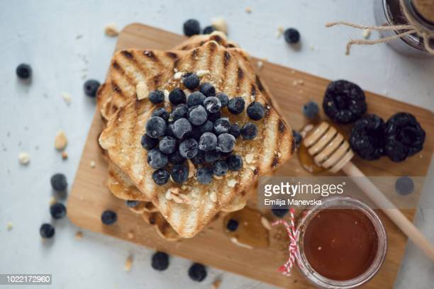 toasted bread with honey and berries - ready to eat stock pictures, royalty-free photos & images