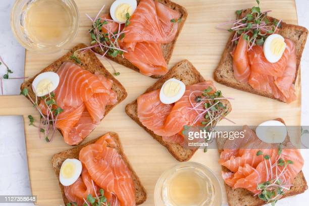 Toasted bread with salmon garnished with quail egg and radish sprouts