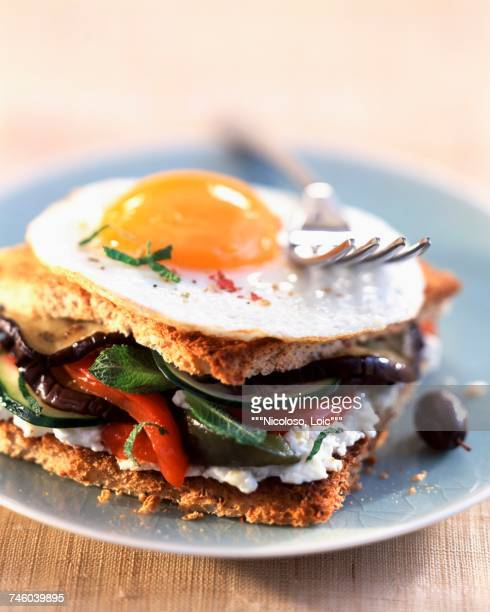 toasted sandwich with fried egg, vegetables and goats cheese - olive pimento stock photos and pictures
