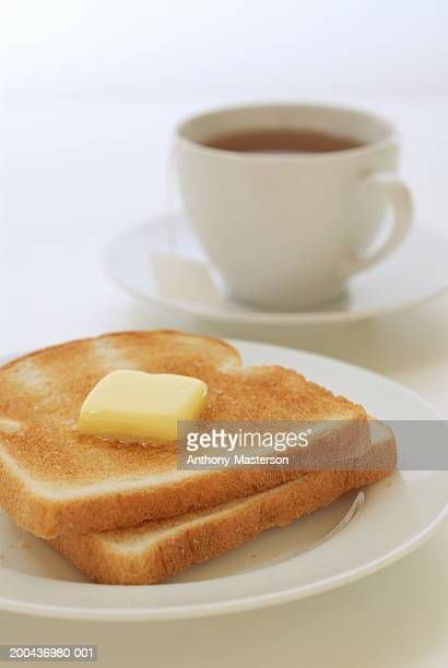 Toasted white bread with pat of butter and cup of tea