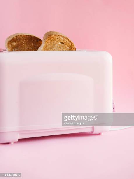 toaster with bread slices against pink background - toaster appliance stock pictures, royalty-free photos & images
