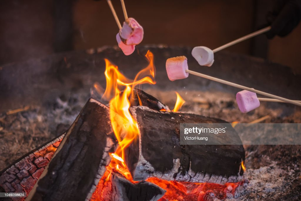 Toasting a marshmallow over an open flame at Christmas market winter wonderland in London : Stock Photo