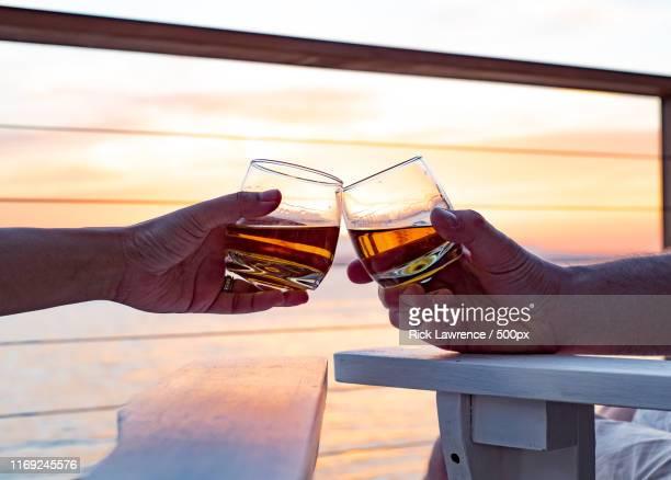 toasting glasses at sunset - bourbon whiskey stock-fotos und bilder