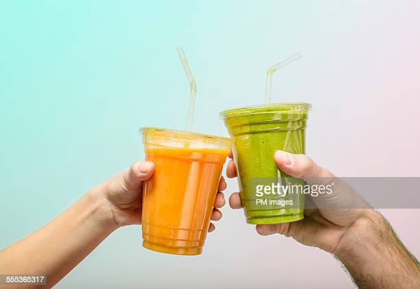 toasting with fruit smoothies - bere foto e immagini stock