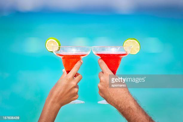 toasting with margarita glasses and tropical drinks - margarita beach stock photos and pictures
