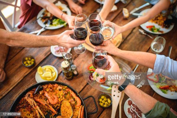 toasting with red wine and water before start of midday meal - spanish culture stock pictures, royalty-free photos & images