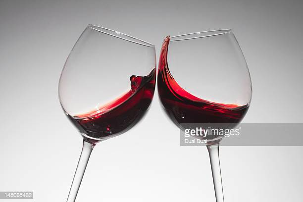 toasting with two glasses of red wine - copa de vino fotografías e imágenes de stock