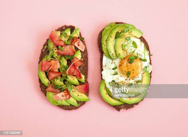 toasts of dark bread with avocado slices, red tomatoes, fried egg and microgreen. top view with pink background. - butter stock pictures, royalty-free photos & images