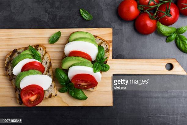 toasts with avocado and caprese salad - avocado toast stockfoto's en -beelden