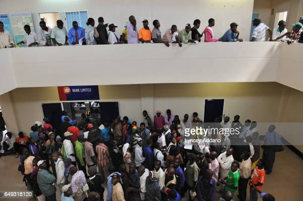 Tobacco growers collect their cash after selling their tobacco at the Boka Auction House Harare Zimbabwe April 17 2012 More than a decade after it...