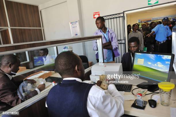 Tobacco growers collect their checks after selling their tobacco at the Boka Auction House Harare Zimbabwe April 17 2012 More than a decade after it...