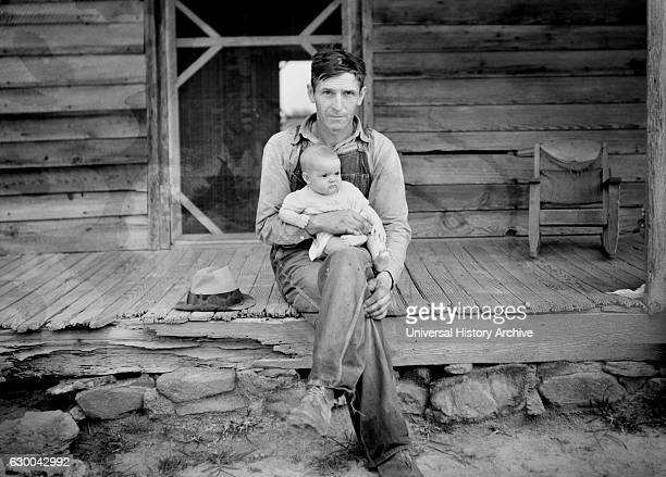 Tobacco Sharecropper with Baby on Front Porch, Person County, North Carolina, USA, Dorothea Lange for Farm Security Administration, July 1939.